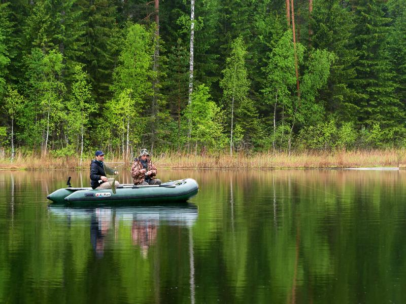 Two men catch fish from an inflatable boat with fishing rods on the lake stock photos