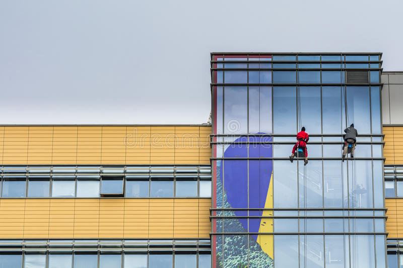 Two men cleaning office building windows in Bucharest royalty free stock image