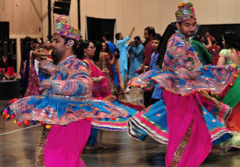 Two Men are dancing in action. Enjoying Hindu festival of Navratri Garba wearing traditional consume. Navratri festival of garba and dandiya dance in Calgary royalty free stock images