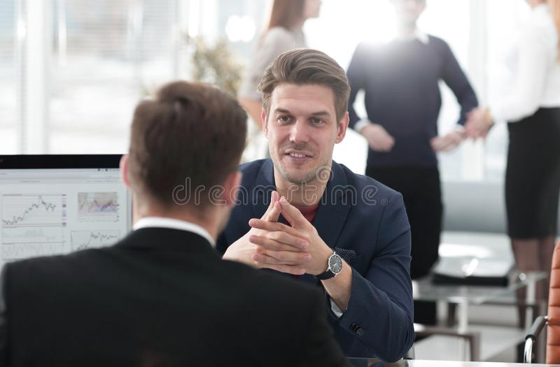 Two men discuss the growth of the company, looking at the rising graph on a computer screen royalty free stock photo