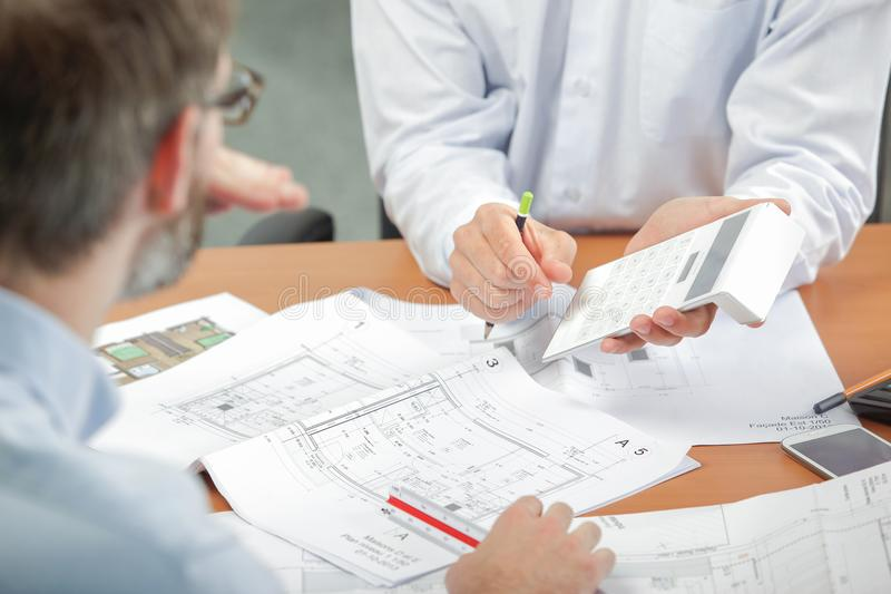 Two men discussing blueprints holding calculator stock photos