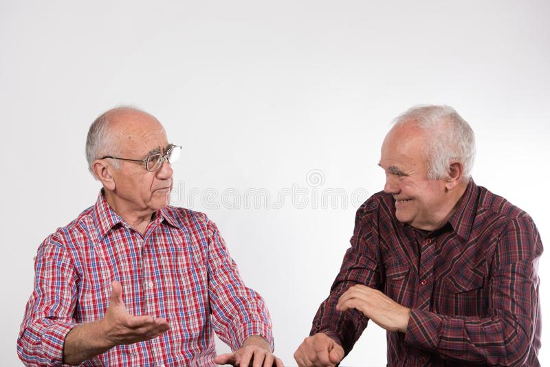 Two men in colorful shirts have discussion stock image