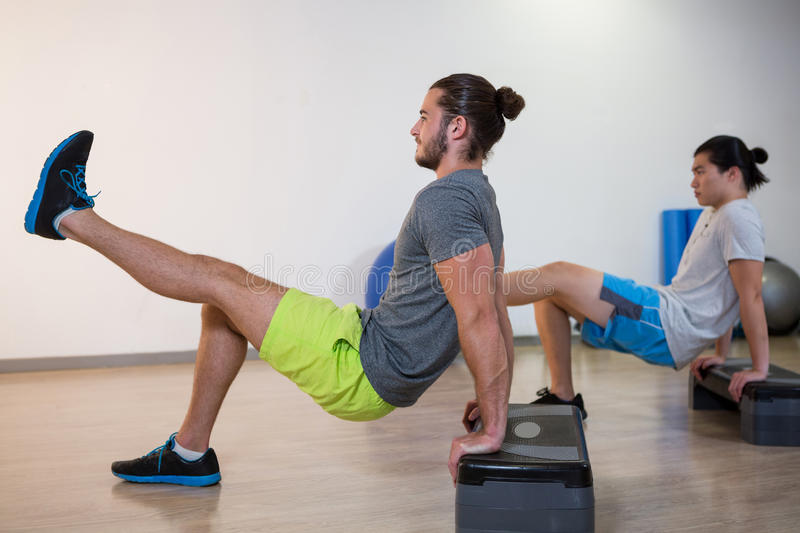 Two men doing aerobic exercise on stepper. In fitness studio stock images