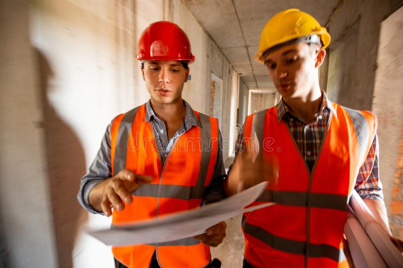 Two men dressed in orange work vests and helmets work with construction documentation inside the building under. Construction royalty free stock images