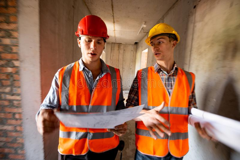 Two men dressed in orange work vests and helmets work with construction documentation inside the building under. Construction royalty free stock photo