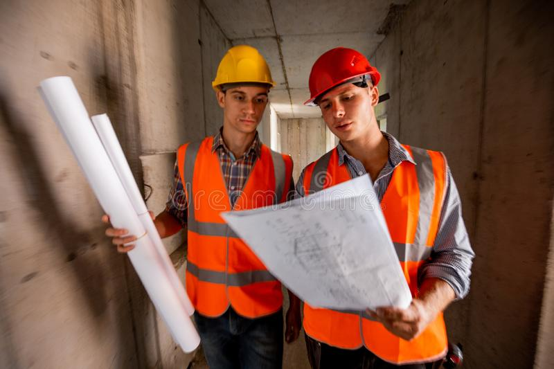 Two men dressed in orange work vests and helmets work with construction documentation inside the building under. Construction stock photo