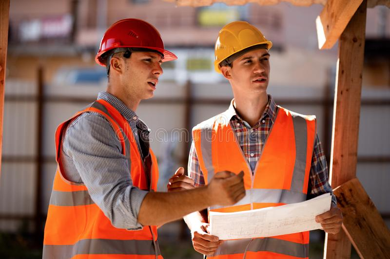 Two men dressed in shirts, orange work vests and helmets explore construction documentation on the building site near. The wooden building constructions stock image