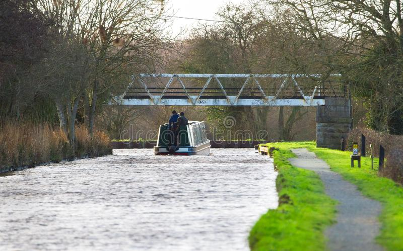 Two men drive a boat down a narrow canal in rural England royalty free stock photography