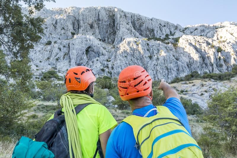 Climbers pointing away. Two men in equipment for mountaineering standing at rock and looking away stock photography