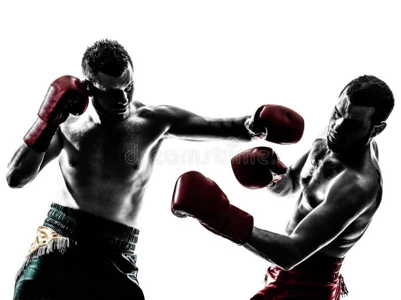 Two men exercising thai boxing silhouette. Two caucasian men exercising thai boxing in silhouette studio on white background stock photo