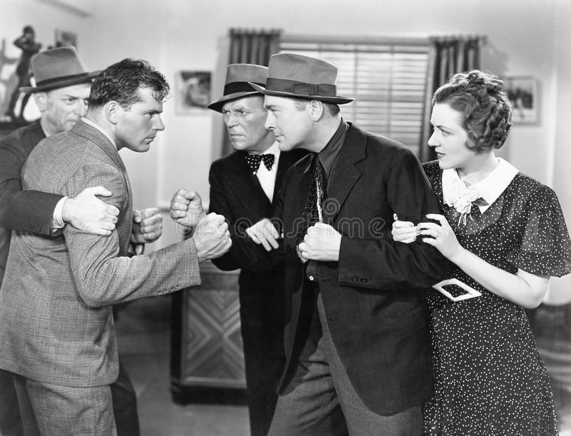 Two men fighting with each other and being held back by a woman and a man. (All persons depicted are no longer living and no estate exists. Supplier grants that stock images