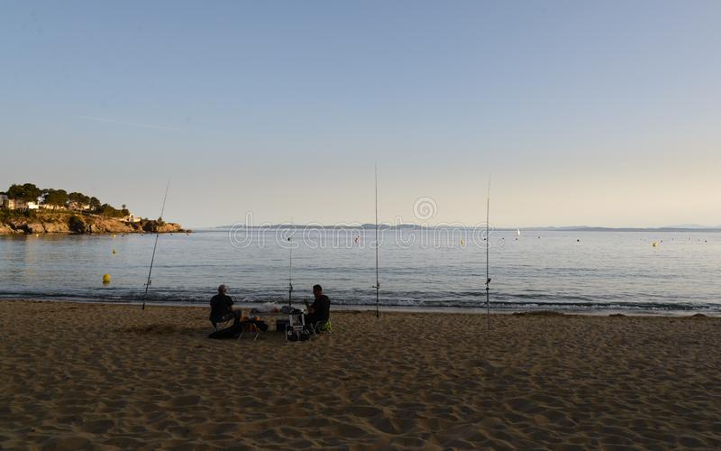 Two men fishing in the beach ,Costa Brava, Catalonia, Spain at the evening royalty free stock images