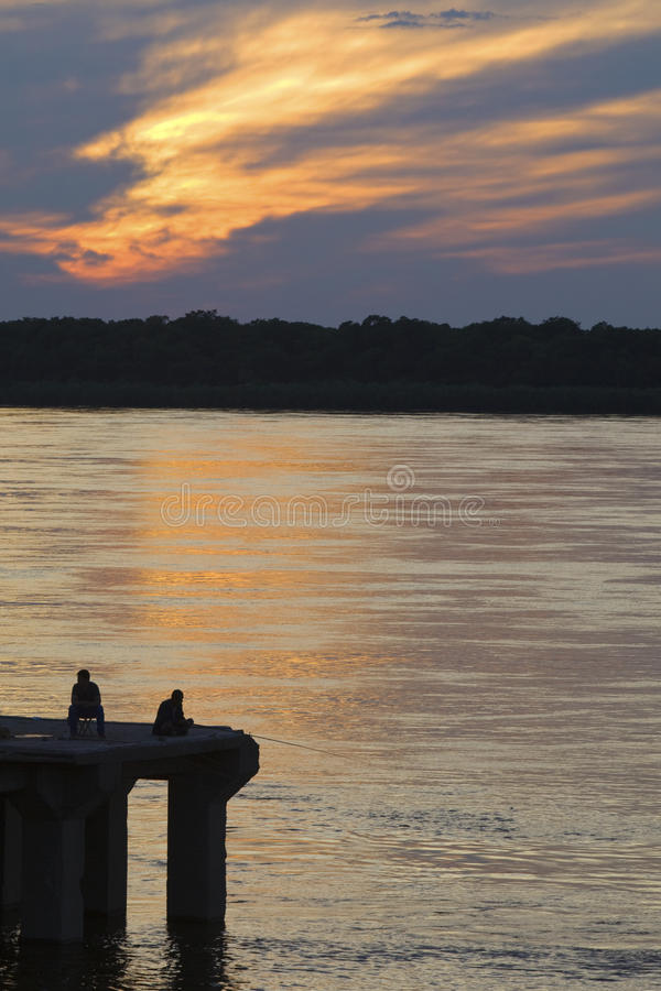 Two men fishing at sunset royalty free stock image