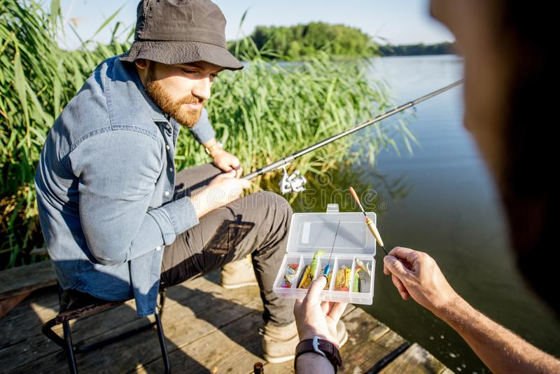 Men fishing on the lake. Two men with fishing tackles during the fishing process on the lake in the morning stock images