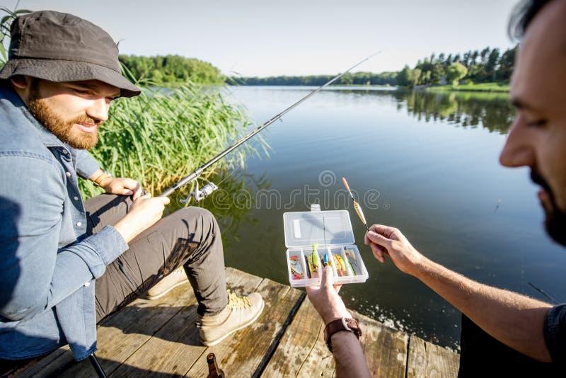 Men fishing on the lake. Two men with fishing tackles during the fishing process on the lake in the morning royalty free stock photo