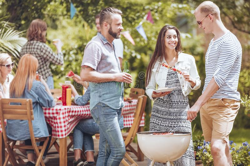 Two men flirting with a beautiful woman while standing next to a. Two men flirting with a beautiful women while standing next to a white grill with shashliks royalty free stock photo