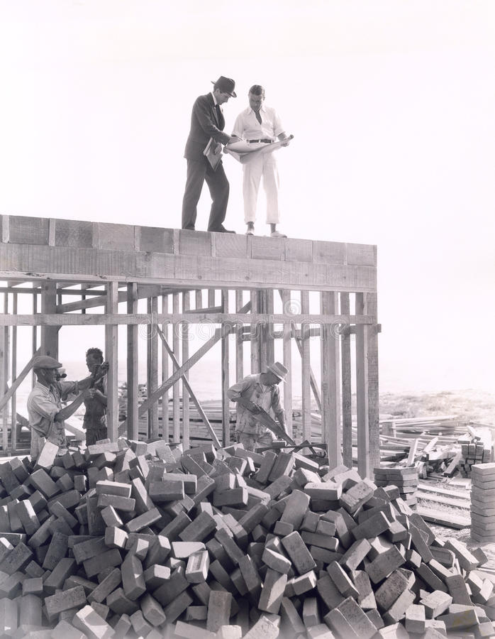 Two men going over blueprints stock photo