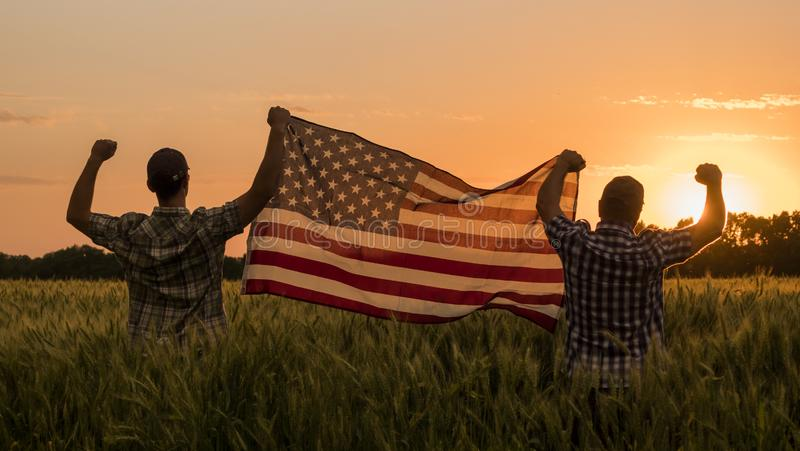 Two men happily raise the American flag over a field of wheat at sunset. 4th of july concept stock photo