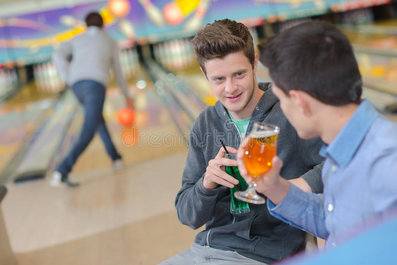 Two men having drink at bowling alley stock photo