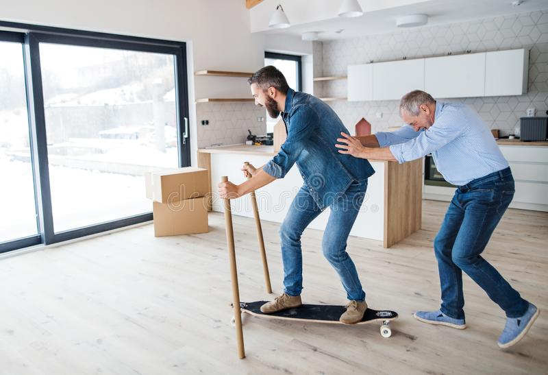 Two men having fun when furnishing new house, a new home concept. royalty free stock images
