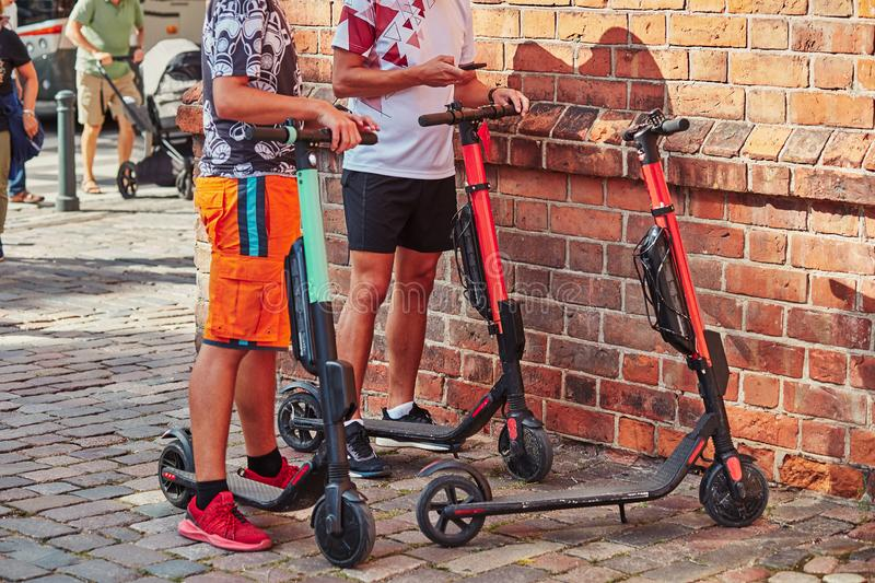 Two men hiring electric scooters using rent service on smartphone royalty free stock photography