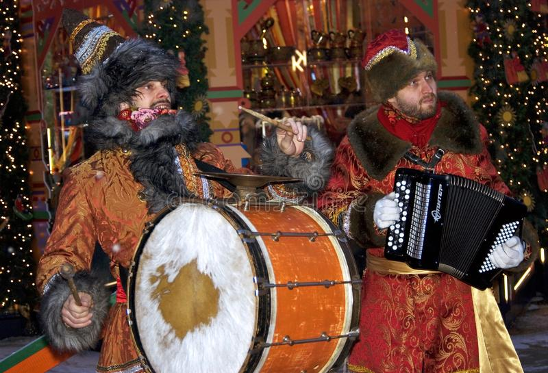 Two men in historical costumes play musical instruments. Drums and accordeon. They are a band performing at Shrovetide - Pancake week - celebration in Moscow royalty free stock images