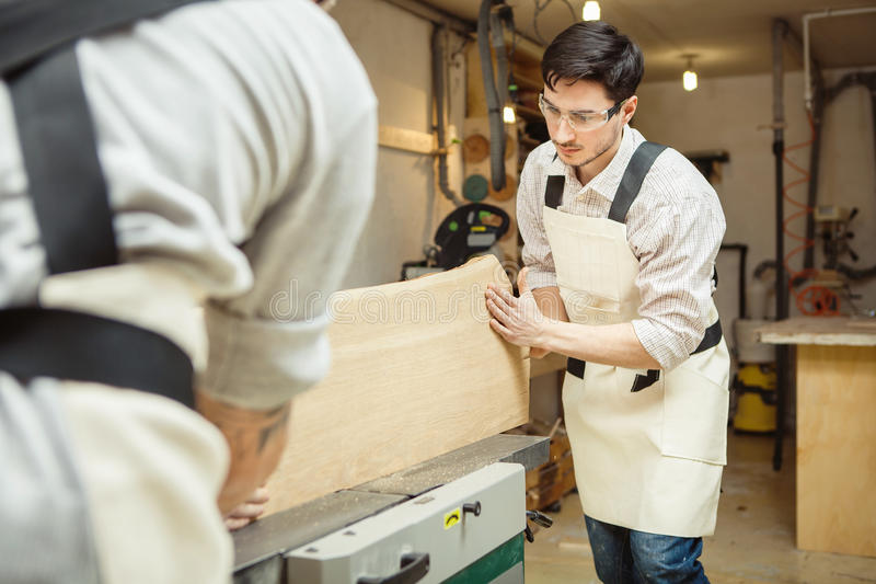 Two men holding timber on woodworking machine. Two man holding timber on woodworking machine. Workplace equipped sleeves for hood. Rounded templates hanging on royalty free stock images