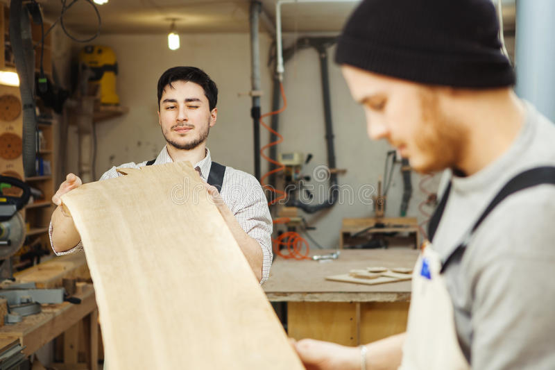 Two men holding timber on woodworking machine. Workplace equipped sleeves for hood. Rounded templates hanging on wall near machine-tool stock images