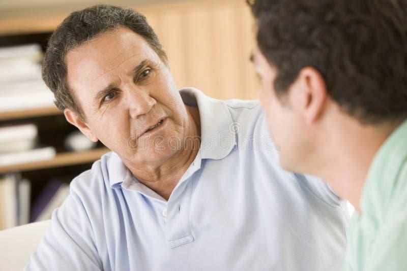 Two men in living room talking stock photo