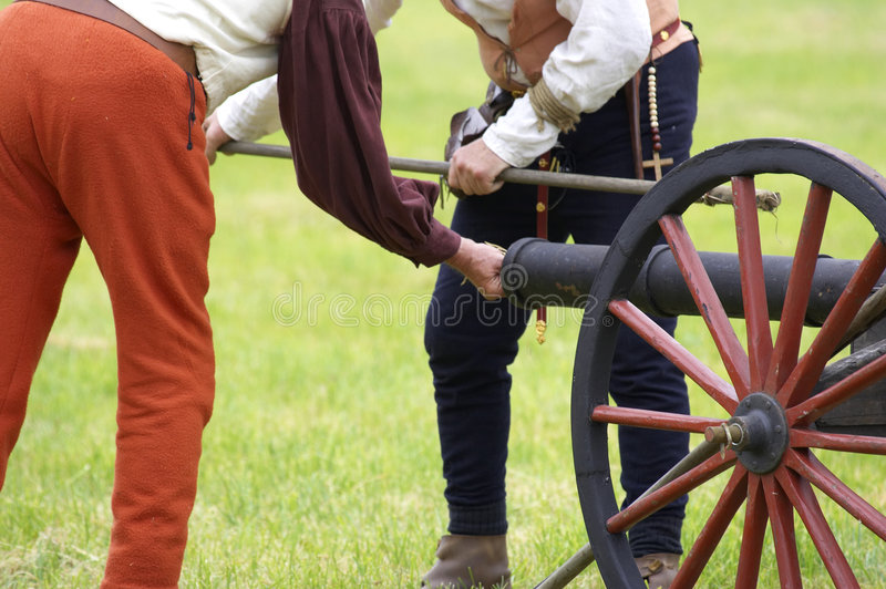 Two men loading a cannon