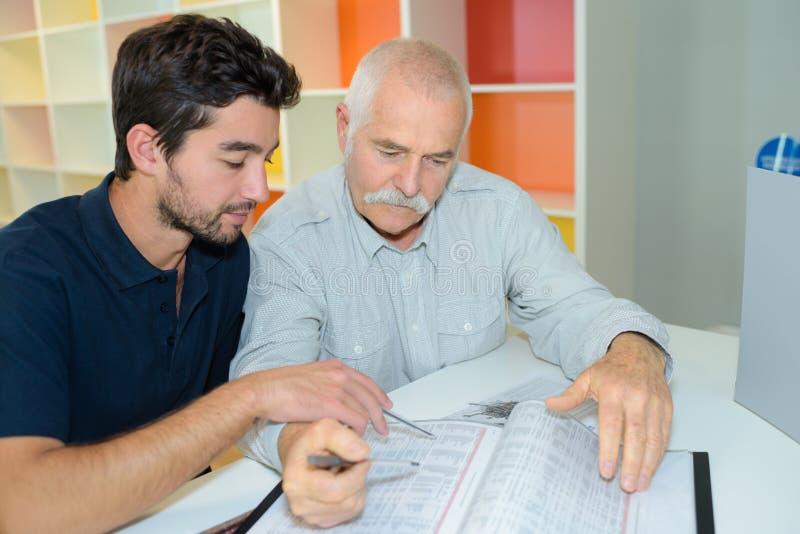 Two men looking through directory. Men royalty free stock image