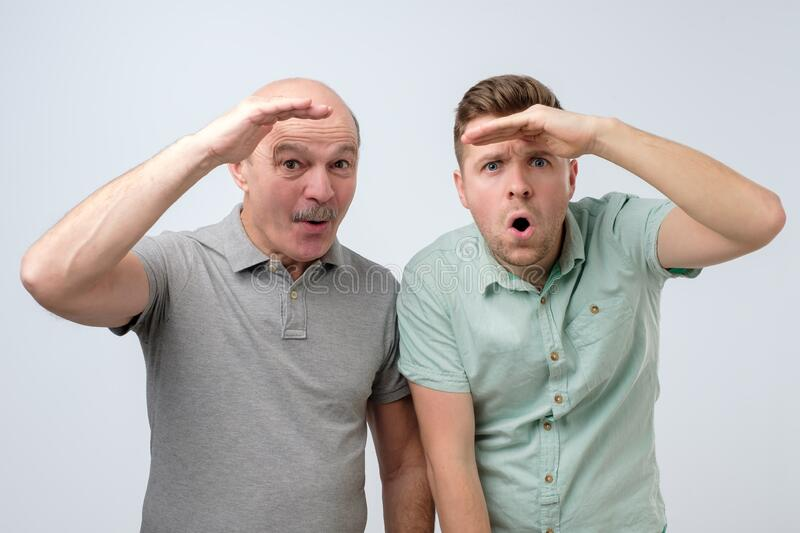 Two men looking forward with big expectations being shocked. royalty free stock photography