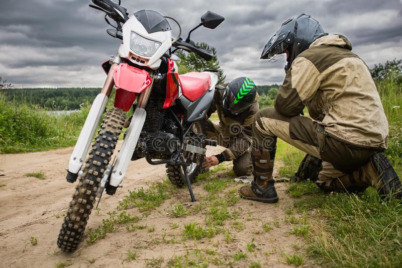 Two men in motorcycle gear checking rear wheel of dirtbike. Adjusting bolt with socket wrench on bike. Riders fixing motorbike, tightening metal parts. View at royalty free stock image