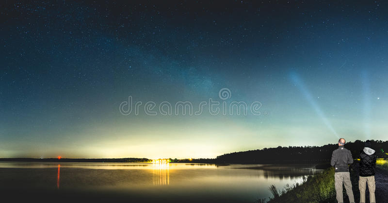 Two men observing beautiful Milky Way shining over lake. royalty free stock photo