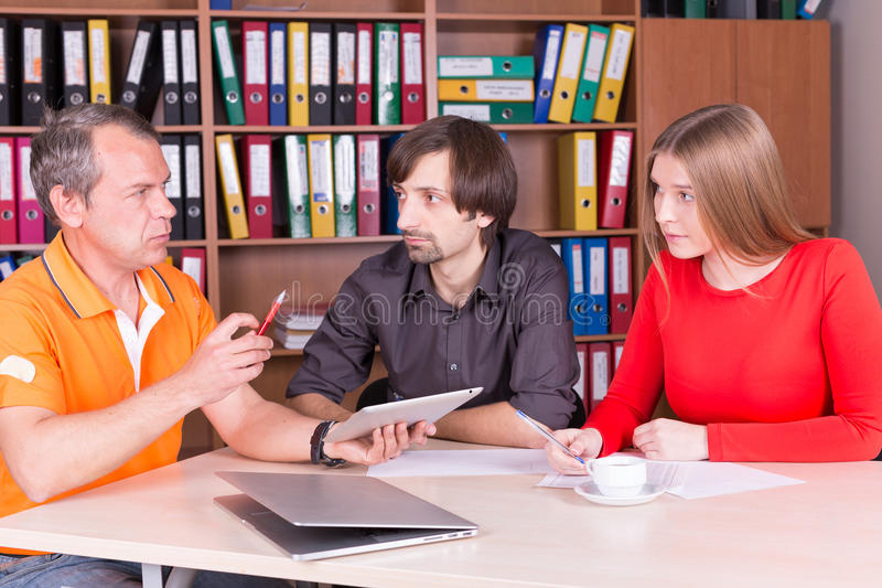 Two men and one woman have meeting in office royalty free stock image