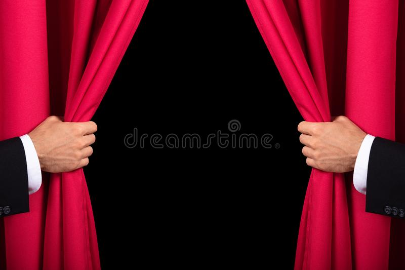 Two Men Opening Red Curtain. Close-up Of Two Men`s Hand Opening Red Curtain stock photo