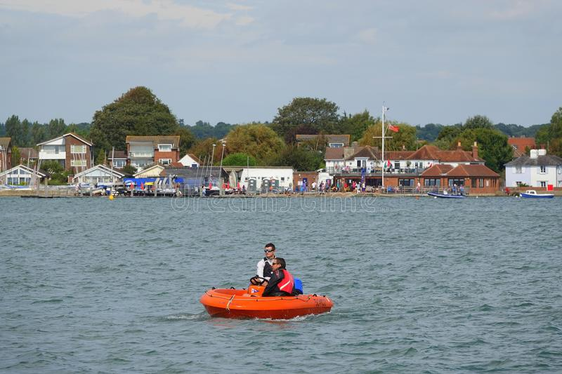 Two men in orange rubber dinghy. Cruising past the sailing club in Emsworth in Hampshire, England royalty free stock image