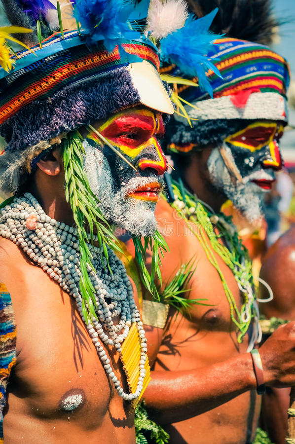 Two of men in Papua New Guinea. Hagen show, Papua New Guinea - circa August 2015: Two native half-naked men with colours on their faces and beards and look ahead stock image