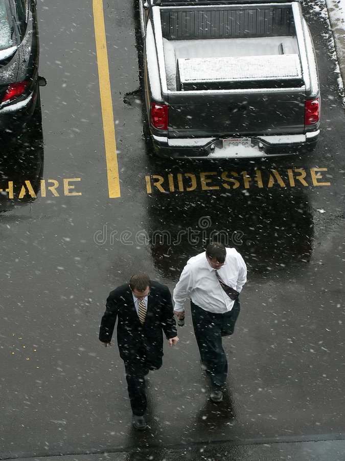 Two men in parking lot. Two men walking across snowy office parking lot royalty free stock photo