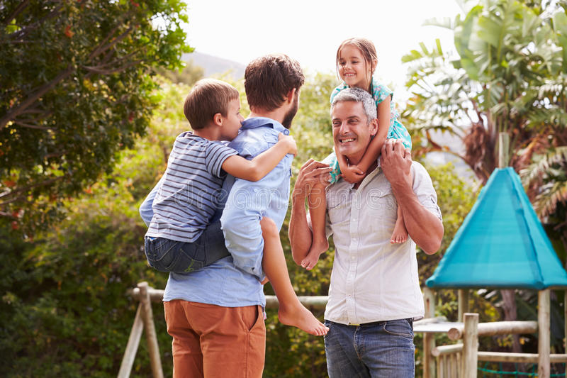 Two men piggybacking kids in a garden stock photo