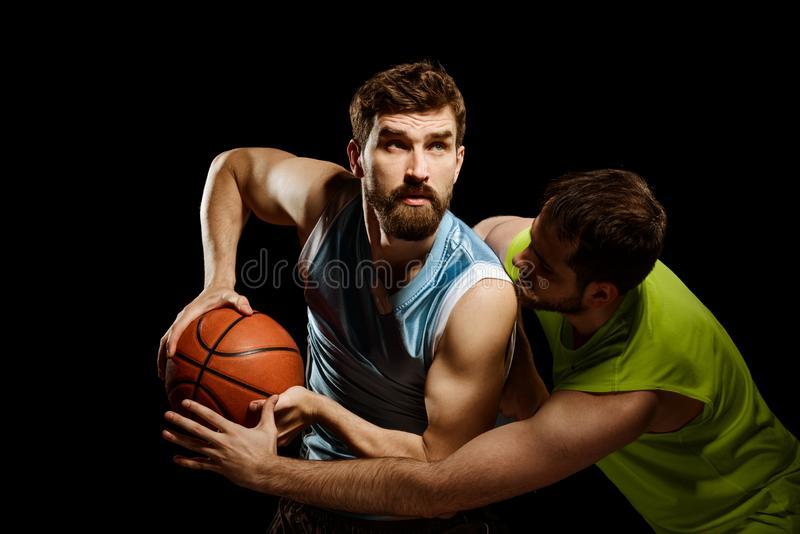 Two men playing basketball. On black. Man in a blue top tank driving to the basket while opposing player attempts to take control over the ball royalty free stock images