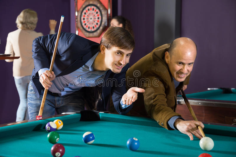 Two men playing billiards stock images