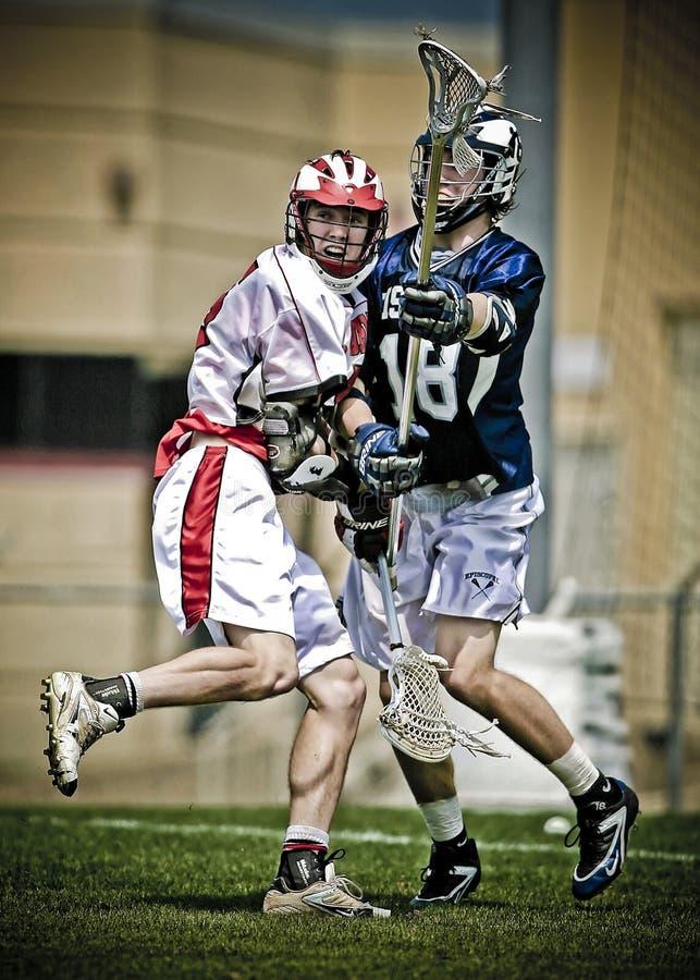 Two men playing lacrosse royalty free stock image