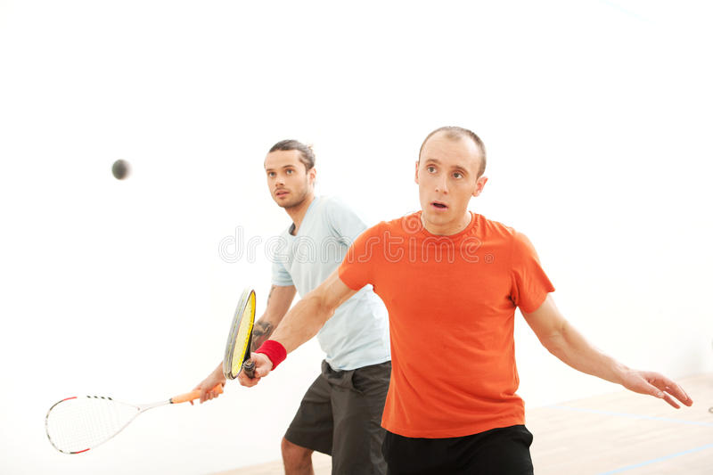 Two men playing match of squash. royalty free stock image