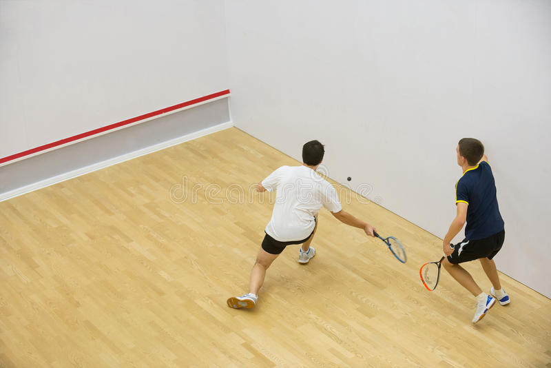 Two men playing match of squash. royalty free stock images