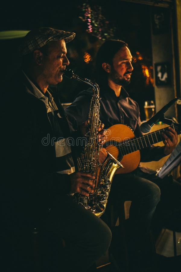 Two Men Playing Saxophone and Acoustic Guitar during Night Time stock images