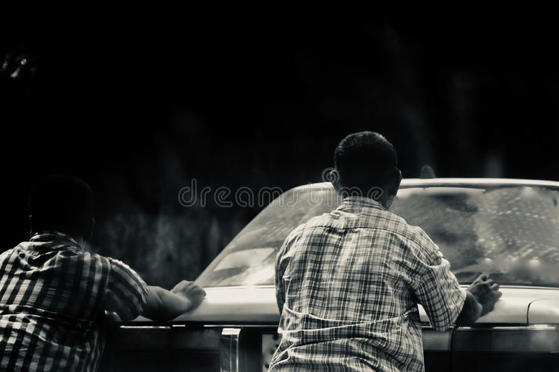 Two men pushing an inactive cars on a city streets in Dhaka. Unique stock photo stock image