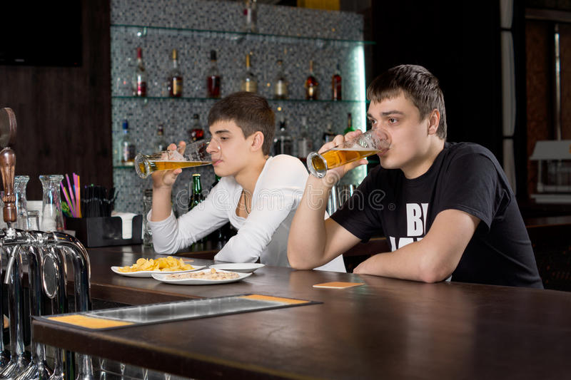 Two men relaxing at the bar drinking beer stock photography