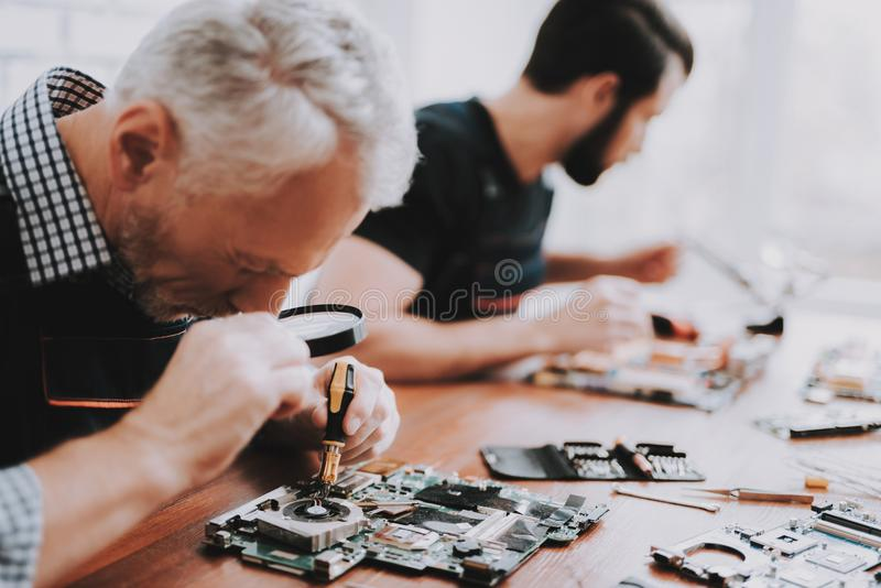 Two Men Repairing Hardware Equipment from PC. Repair Shop. Worker with Tools. Computer Hardware. Young and Old Workers. Modern Devices. Digital Device. Laptop stock photo