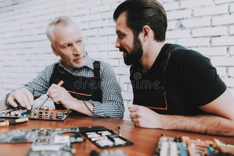Two Men Repairing Hardware Equipment from PC. Repair Shop. Worker with Tools. Computer Hardware. Young and Old Workers. Soldering Iron. Digital Device. Laptop royalty free stock photo